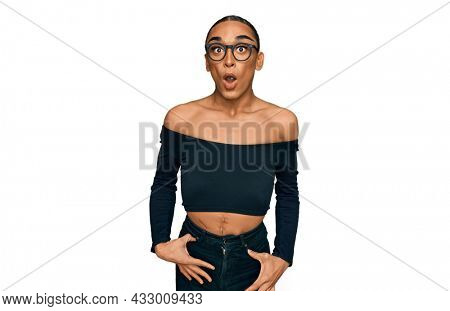 Hispanic transgender man wearing make up and long hair wearing women clothes afraid and shocked with surprise expression, fear and excited face.