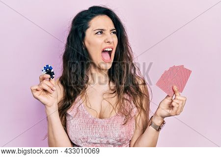 Young hispanic woman playing poker holding casino chips and cards angry and mad screaming frustrated and furious, shouting with anger. rage and aggressive concept.