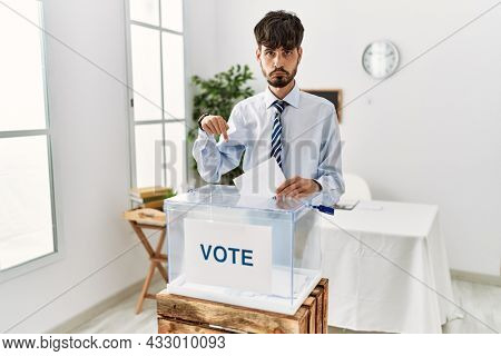 Hispanic man with beard voting putting envelop in ballot box pointing down looking sad and upset, indicating direction with fingers, unhappy and depressed.
