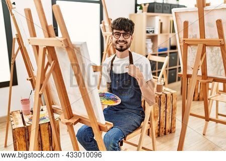 Hispanic man with beard at art studio pointing finger to one self smiling happy and proud