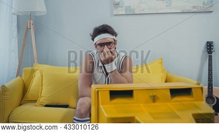 Bored Man In Retro Sportswear Sitting On Couch And Watching Tv