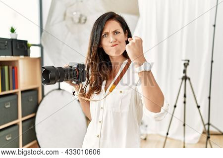 Beautiful caucasian woman working as photographer at photography studio angry and mad raising fist frustrated and furious while shouting with anger. rage and aggressive concept.