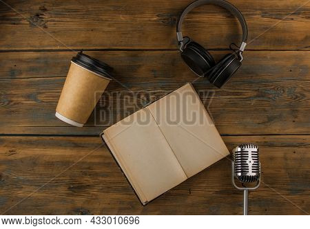 Open book with blank page, headphone and a cup of coffee in a disposable paper cup on a wooden table. Remote education concept. Top view