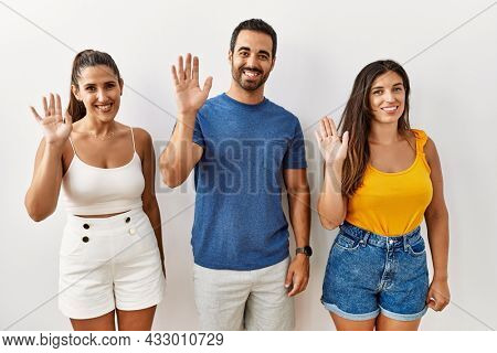 Group of young hispanic people standing over isolated background waiving saying hello happy and smiling, friendly welcome gesture