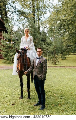 Young Married Couple On Ranch, Bride In White Dress With Bouquet Sits Astride Horse, Groom In Suit H