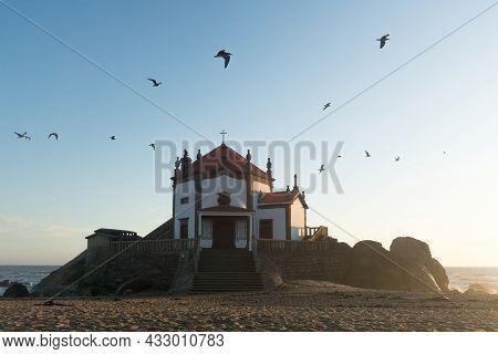 Capela Do Senhor Da Pedra Or Lord Of The Rock Chapel At Sunset With Birds In The Sky, Miramar, Portu