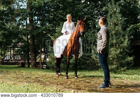 Outdoor Ranch Wedding. Happy Young Bride In White Dress With Bouquet Sits Astride Horse And Looks At