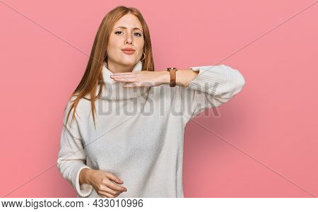 Young irish woman wearing casual winter sweater cutting throat with hand as knife, threaten aggression with furious violence
