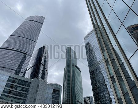 Facade Of Modern Skyscraper With Glass Walls. From Below Of Contemporary Tall Skyscraper With Glass