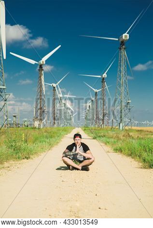 Guy With A Tattoo All Over His Arm Sits In The Middle Of The Road Between The Wind Turbines. Scenic