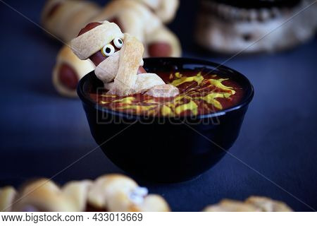 Fun Food For Kids. Mummy Hot Dogs On A Blue Rustic Table Sitting Inside Of A Bowl Of Ketchup And Mus