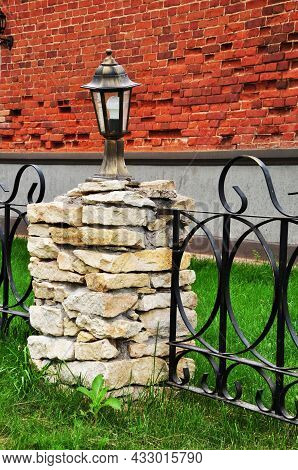 Small Lighting Lantern On A Base Of Flat Stones. Pole With A Lantern\nnear A Stone Wall.