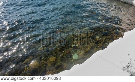 Clean Water Of A Non-freezing River. Stones Are Visible At The Bottom. Sun Glare And Ripples On The