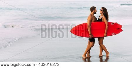 Surfing On The Shore Of The Paradise Island. A Couple In Love On Vacation On The Ocean. A Married Co
