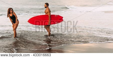 A Couple In Love On Vacation On The Ocean, Panorama. Surfing On The Shore Of The Paradise Island Of