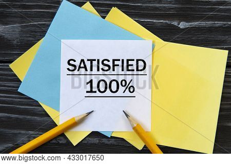 Satisfied 100% - Words On Note Paper On A Black Background. Info Concept