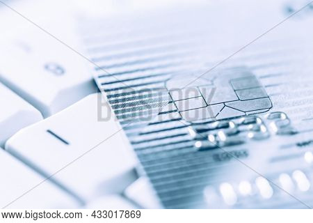 Closeup image of o credit card in silver and blue tone, selective focus, keyboard in background