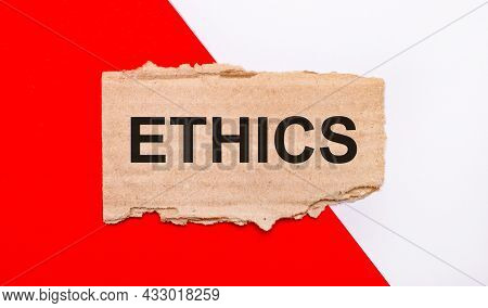 On A White And Red Background, Brown Torn Cardboard With The Text Ethics