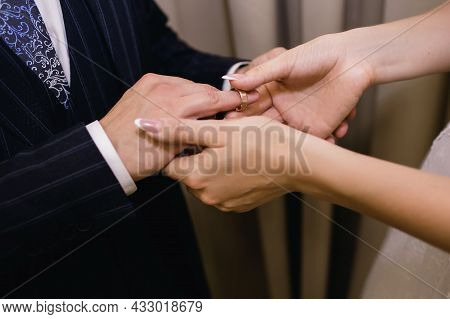 The Bride Puts A Gold Wedding Ring On The Groom's Finger Close-up. The Bride Gently Holds The Groom'
