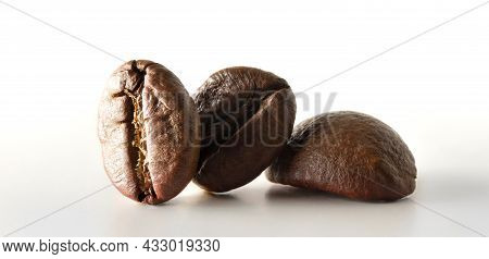 Macro View Of Three Coffee Beans Reflected On White Table And White Background. Front View. Horizont