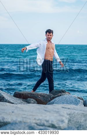 Side View Of Serene Stylish Male In White Shirt Walking Along Rocky Coast On Background Of Blue Sea