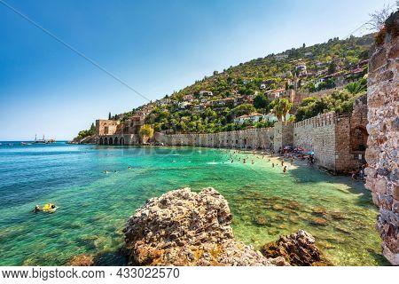 Alanya, Turkey - July 21, 2021: Tourists swimming in the Mediterranean Sea at the city walls of Alanya, Turkey.