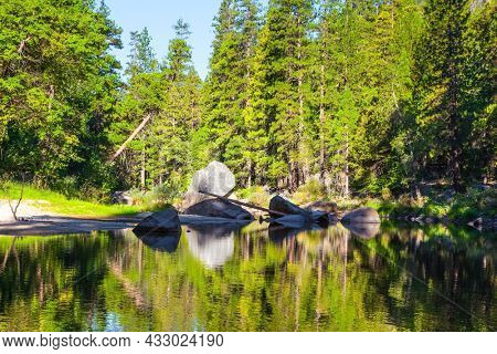 Charming little lake in the Yosemite Valley. The shady forest is reflected in the smooth water. Yosemite Park is located on the slopes of the Sierra Nevada