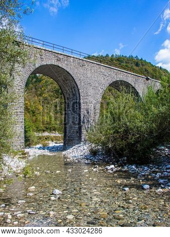 Travel to Slovenia. The magical beauty of the Julian Alps. Bridge - viaduct over the shallow rocky river Idrija. Autumn colors of mountains and forests.