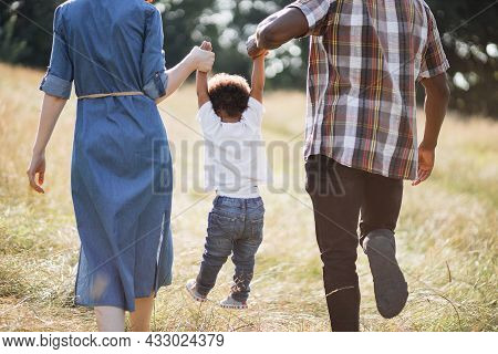 Back View Of Mixed Race Parents Walking With Little Son On Summer Field And Holding Hands. Close Up