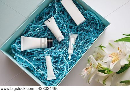 Beauty Box With Blue Filler And Miniatures And Samples Of Caring Cosmetics And Alstroemeria On A Whi
