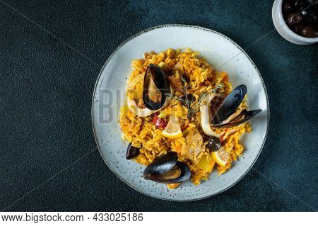 Classic Dish Of Spain, Seafood Paella In Plate On Blue Background Top View. Spanish Paella With Shri