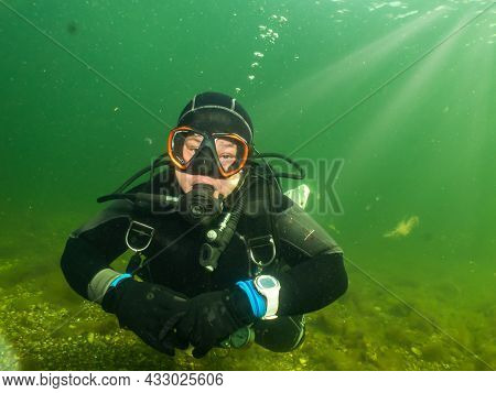 A Female Scuba Diver Lit Up By Rays Of Sunlight Penetrating The Water. Picture From The Sound Betwee