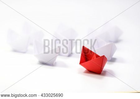 Leadership Concept With One Red Paper Ship Leading Among White. Paper White Ships Swim Behind The Re