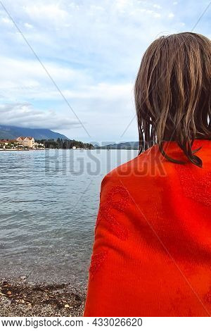 Rear View Of A Girl With Loose Wet Hair In A Bright Towel Looking At The Ocean