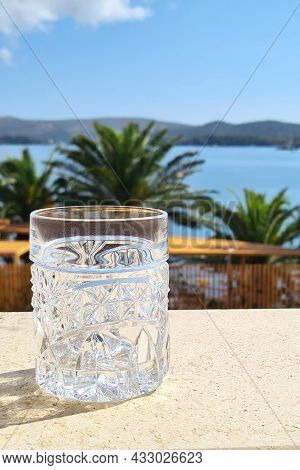 Beautiful Crystal Glass On The Background Of The Seascape And Palm Trees