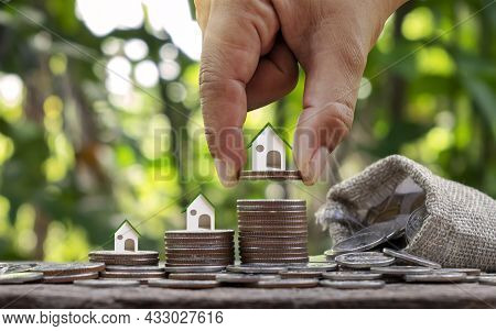 House Plan On Pile Of Coins And Coin Hand With Financial Concept. High Growth Investment And Real Es