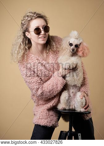 Curly Girl And Poodle With Glasses. A Dog Similar To Its Master. Portrait In Studio. Modern, Joke, B