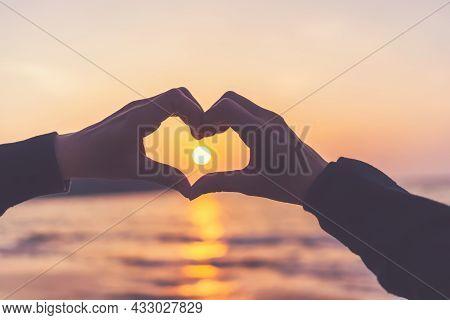 Female Hands Heart Shape On Nature Bokeh Sun Light Flare Wave And Blur Tropical Sunset Beach Abstrac