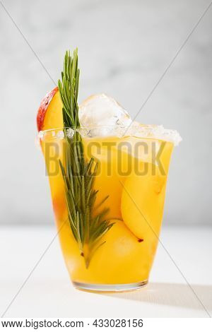 Homemade Organic Cold Peach Juice With Ice, Green Rosemary Twig, Sugar Rim, Fruit Slices In Wet Glas