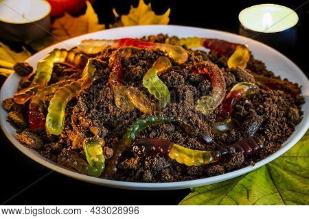 Dish For Decorating Table Halloween. In White Plate Marmalade Worms In Ground Made Of Crumbled Choco
