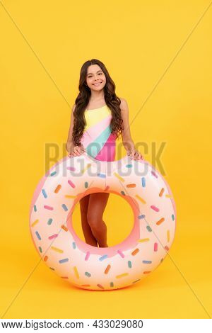 Child In Swimming Suit With Doughnut Inflatable Ring On Yellow Background, Summer.