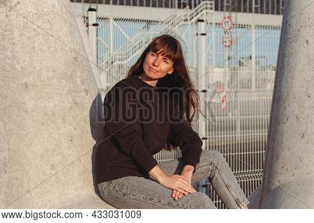 Young Brunette Woman In Black Hoodie Sitting On A Breakwaters.
