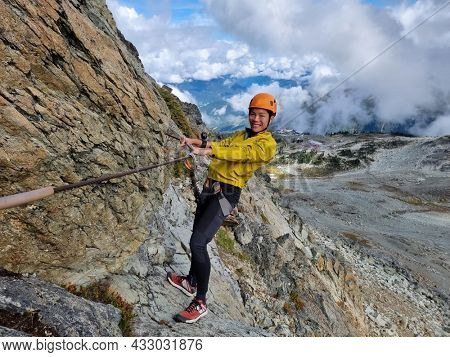 Via Ferrata climbing guided tour excursion happy Asian woman tourist hanging from rope at high pass on mountain side on Whistler peak, BC, Canada Travel.