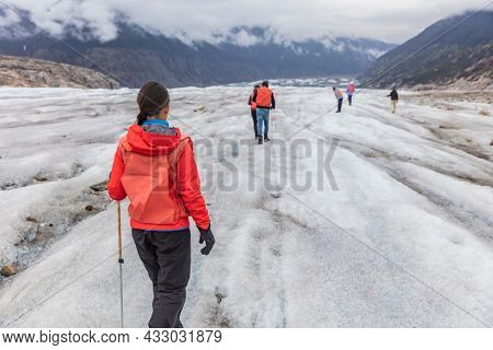 Alaska glacier hiker woman on cruise ship excursion. tourist girl walking with group of hikers on blue ice adventure nature vacation, popular activity in Alaska holidays.