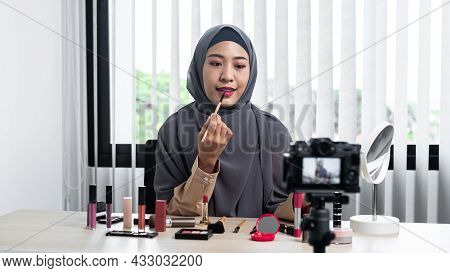 Asian Muslim Woman Beauty Blogger Applies Lipstick On Her Mouth And Making Videos To Review Cosmetic