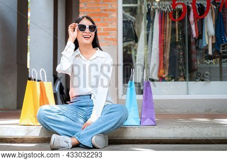 Asian Shopaholic Woman Wearing Sunglass With Many Colorful Shopping Bags And Sitting To Rest After M