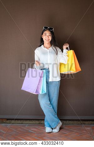 Asian Shopaholic Woman Wearing Sunglass Headband With Many Colorful Shopping Bags In Both Hands Afte