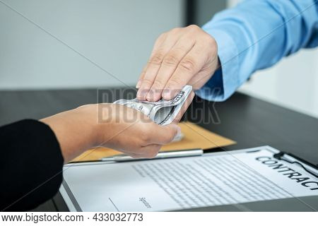 Close Up Of Man Employee Receiving Bribe Dollars In His Hands From Businessman After Signing The Con