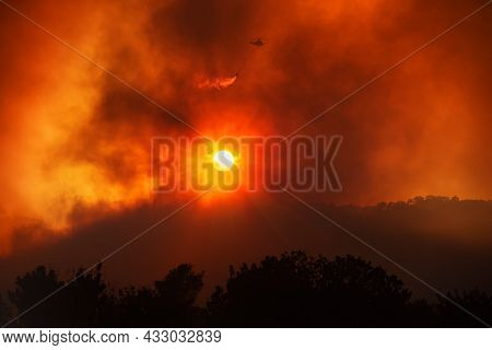 Helicopter Dropping Water From The Bucket, Fighting Forest Fire. Dramatic Landscape Against The Sett