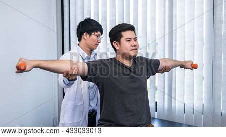 Young Asian Physiotherapist Stretching The Arms Of Man Patient Holding A Dumbbell In Hands During Re